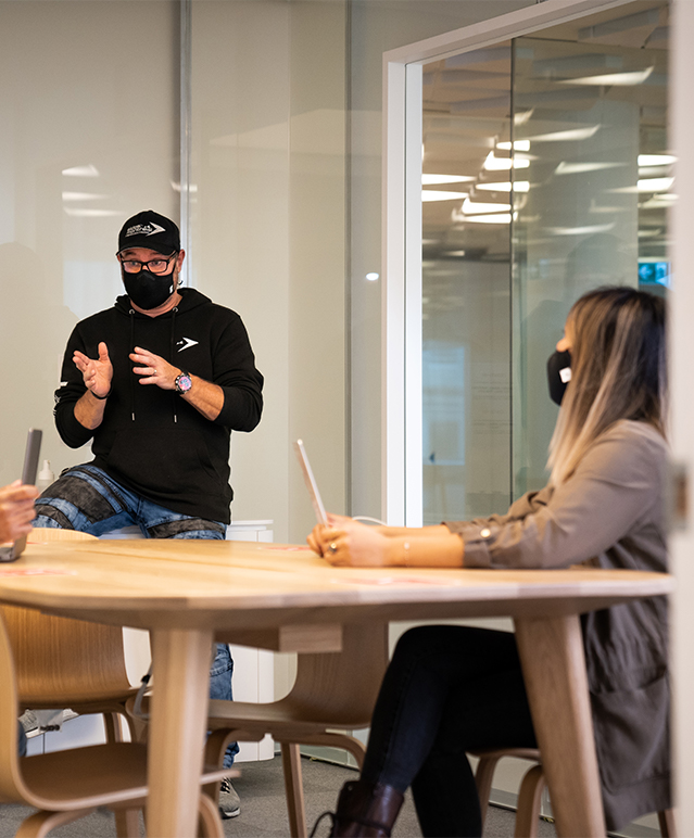 Developers in a meeting room, having a discussion around a table