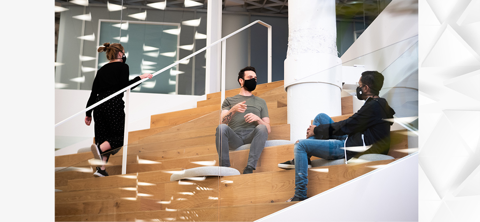Two developers sitting on a stairway and having a discussion, while a colleague goes up the stairs