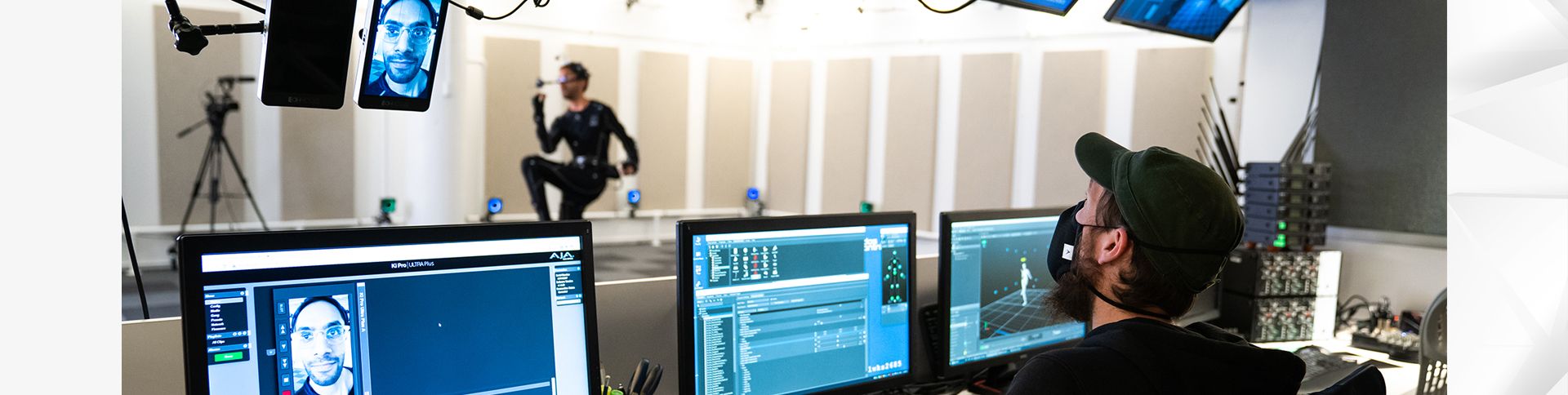 Actor doing stretches in a motion capture room, while the motion capture specialist monitors the session on his computer screen