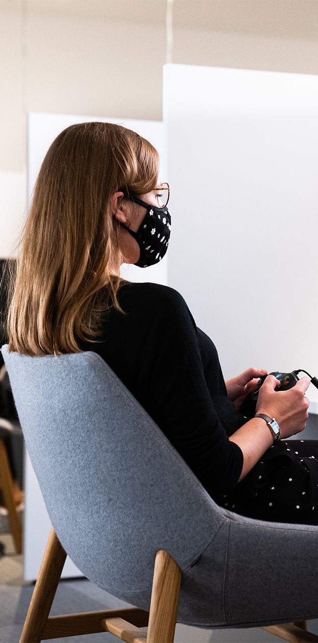 Woman playing Shadow of the Tomb Raider in a playtest room, with a controller in her hands