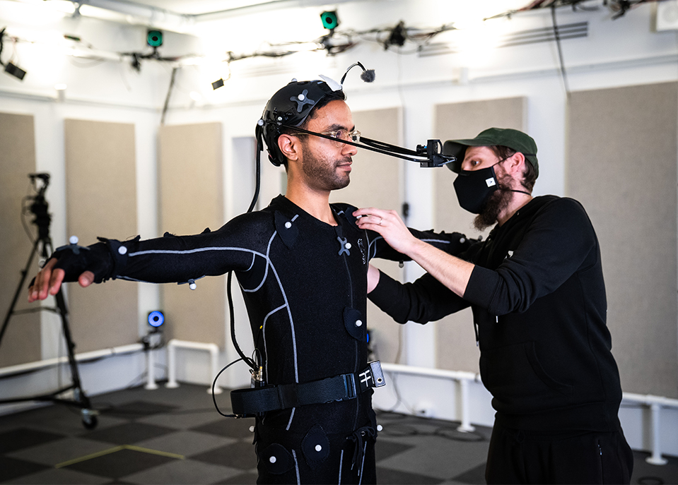 Motion capture specialist adjusting the suit of an actor in t pose